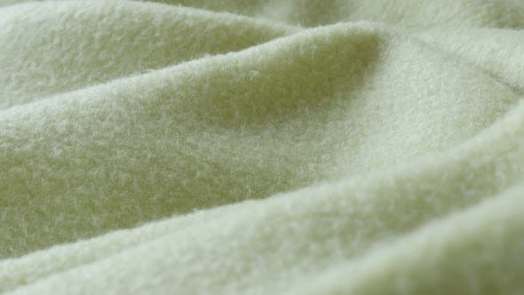 Thumbnail for Gathers of warming green polar fleece blanket close-up 4K video