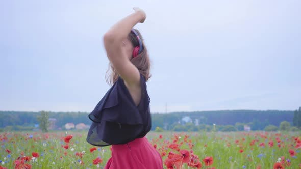 Thumbnail for Pretty Young Woman Wearing Headphones Listening To Music and Dancing in a Poppy Field Smiling