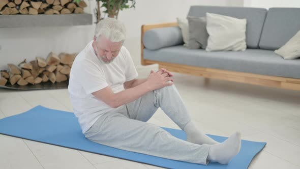 Old Man Having Knee Pain on Yoga Mat at Home