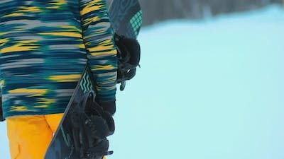 Snowboarder Is Carrying a Snowboard. Snowboard Equipment in the Hands of an Athlete. Close-up.