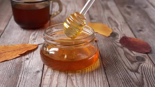 A Jar of Honey with Dipper on Rustic Table