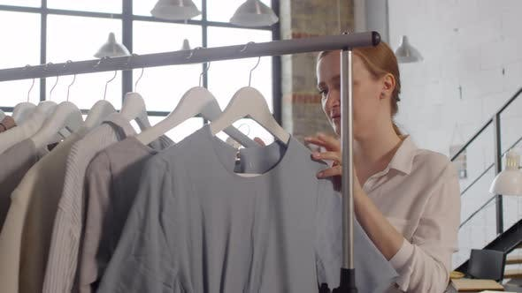 Thumbnail for Beautiful Female Designer Smiling and Posing for Camera beside Garment Rack