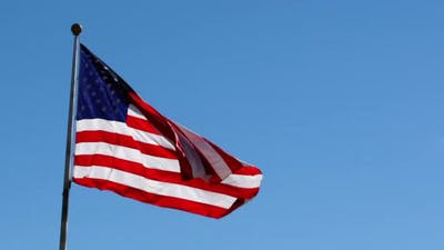 American Flag waving against a blue sky