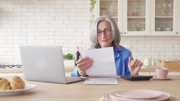 Older Woman Holding Bill Using Calculator Laptop Managing Finances at Home