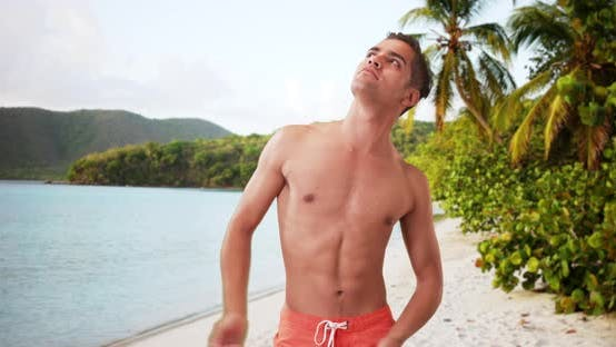 Thumbnail for Happy Millennial Hispanic man posing on beach and laughing during vacation