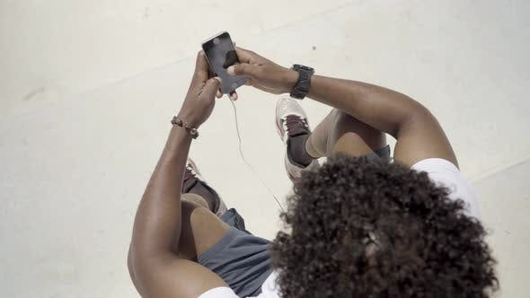 Thumbnail for African American Man with Smartphone Sitting Outdoor