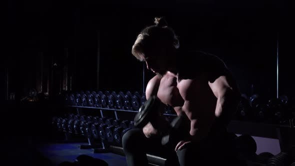 Thumbnail for Handsome Power Athletic Man in Gym Sitting and Using Dumbbell