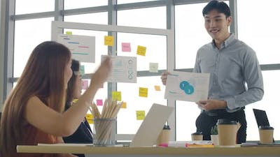 Asian businessman presenting to colleagues at a meeting.