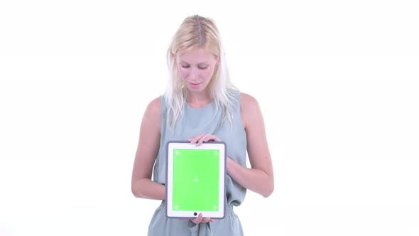 Thumbnail for Happy Young Beautiful Blonde Woman Thinking While Showing Digital Tablet