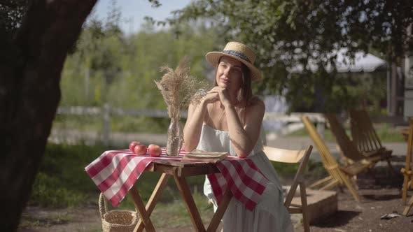 Thumbnail for Young Girl in a Straw Hat and White Dress Sitting at the Small Table and Looking at the Camera