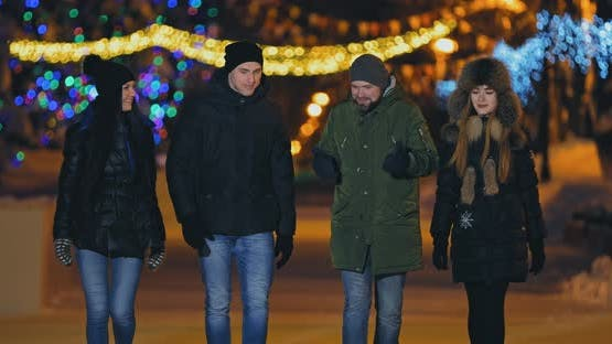 Young and Happy Guys and Girls Walk Along a Winter Night Street