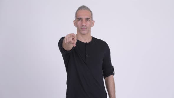 Handsome Persian Man Pointing To Camera Against White Background
