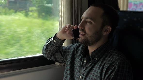 Cover Image for Handsome Man Talking on Mobile Phone in Train