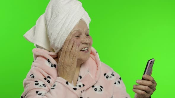 Thumbnail for Elderly Grandmother in Bathrobe. Old Woman Using Mobile Phone for Video Call