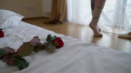 Female Legs Are Stretched Out on Their Toes Near the Bright Window in the Bedroom