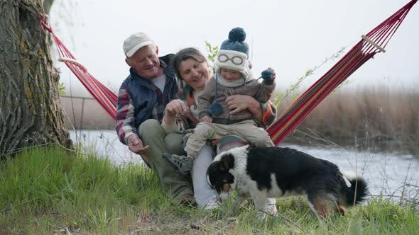 Thumbnail for Parenthood, Cheerful Married Couple, Happy Grandparents Have Fun with Their Grandson Playing with a