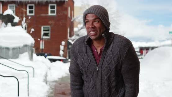 Thumbnail for African-American man standing in the snow outside on frosty morning