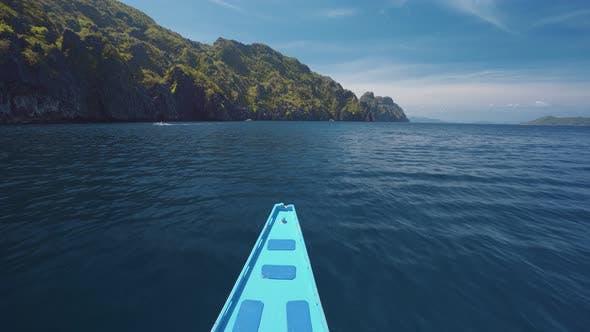 El Nido, Philippines. Island Hopping Blue Boat on Speed Approaching Exotic Karst Limestone Island on