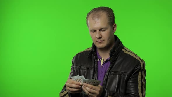 Thumbnail for Man Employee in Jacket Counts Dollar Cash Banknotes and Puts Money To His Pocket. Money Cash Income