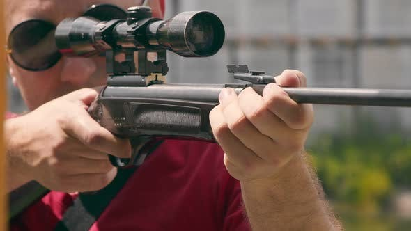 Close Up of the Face of a Man Aiming While Looking Into an Optical Rifle Sight.