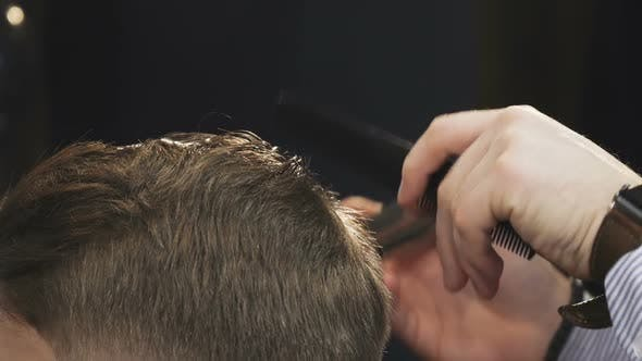 Cover Image for Cropped Close Up of a Barber Cutting Hair of His Client with a Trimmer