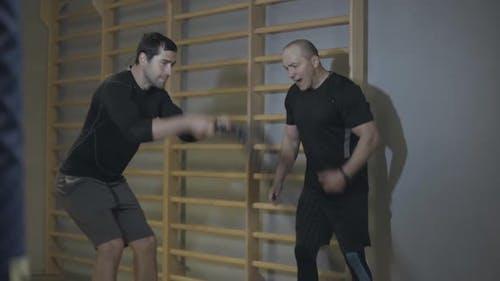 Männlicher Trainer unterstützt junge Brünette Mann Training mit Crossfit Seilen. Gesund gutaussehend Kaukasisch