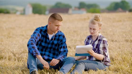 Thumbnail for Agriculture - Female and Male Farmers Talking at Wheat Field During Harvesting