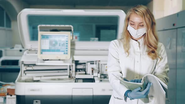 Portrait of a Lab Worker with a Research Folder in Her Hands. Ladorant Reviews Research Records in