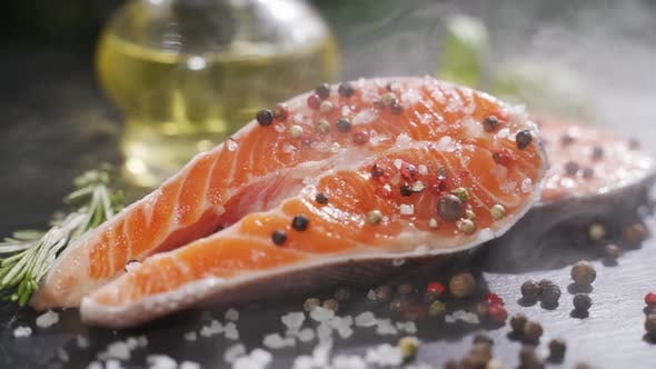 Salmon Fillet Red Fish with Pepper Salt and Rosemary on a Stone Board
