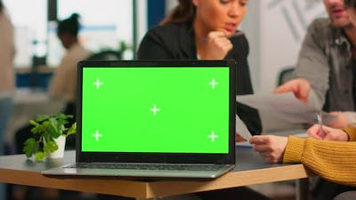Laptop with Green Screen Ready for Presentation Placed on Desk