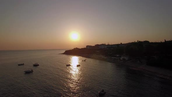 Thumbnail for Sunset Scene of Resort and Sea with Boats, Aerial. Trikorfo Beach in Greece