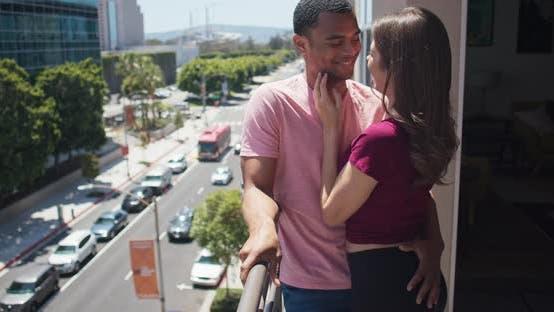 Thumbnail for Paar lachen und lächelnd einander beim Stehen auf Balkon in der Stadt