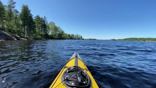 Sports Kayak Sails Along Tranquil Lake Water Past Island