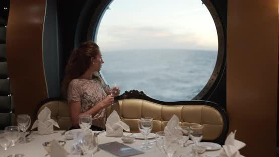 Thumbnail for Woman Watching Sunset From Window On Luxury Cruise Ship with a Glass of Winein in Restorante