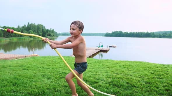 Thumbnail for Boy in Summer Swimming Trunks Pours Water on His Younger Brother Having Fun in the Park on the Grass