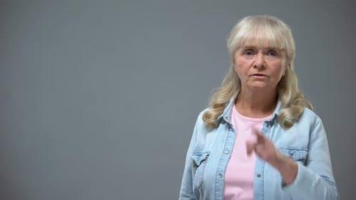 Unhappy Elderly Female Showing Quiet Gesture at Camera, Shame Concept, Prejudice