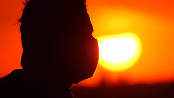 Thumbnail for Silhouette Profile of a Young Man in a Mask. Male Removes a Protective Disposable Medical Mask From