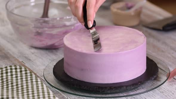 Thumbnail for The process of decorating a cake with purple cream cover.