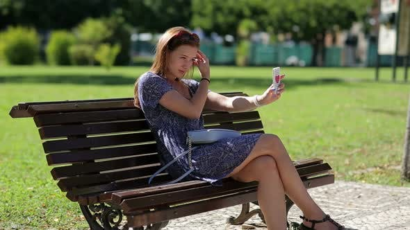 Thumbnail for Young Beautiful Woman Make Selfy Holding Mobile Phone in Hand and Sitting on the Bench in the Park