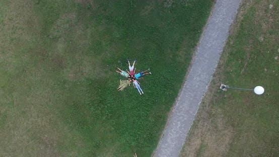 Belles jeunes amis formant une forme d'étoile couchée dans l'herbe