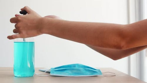 Asian woman using alcohol gel hand sanitizer wash hand before wear mask for protect coronavirus.