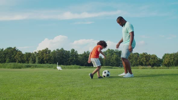 Thumbnail for Family with Child Playing Football Game Outdoors