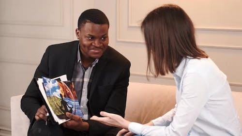 Patientin schaut sich Bilder mit Psychologin im Büro an