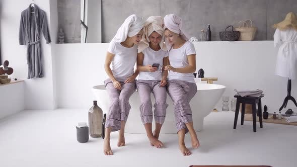 Cover Image for Three Positive Girlfriends in the Same Pajamas and Towels on Heads Spending Time Together at Home