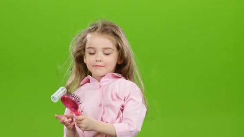 Child Removes the Curlers and Starts Combing His Long Hair. Green Screen