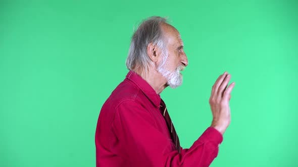 Cover Image for Portrait of Happy Old Aged Man 70s Waving Hand and Communicates with Someone, Isolated Over Green