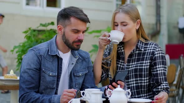 Thumbnail for Lovely Happy 30-Aged Couple in Casual Clothes Drinking Tea in Street Cafe and Fascinate