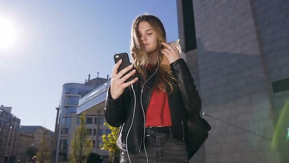 Thumbnail for Attractive Young Woman with Long Hair in Headphones Using Smartphone