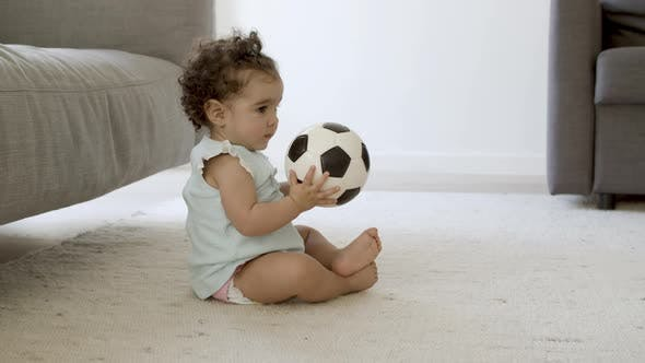 Focused Little Girl Sitting on Carpet Playing with Ball at Home
