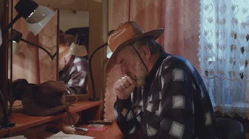 Senior Man Sitting at Mirror Coughing and Using Handkerchief